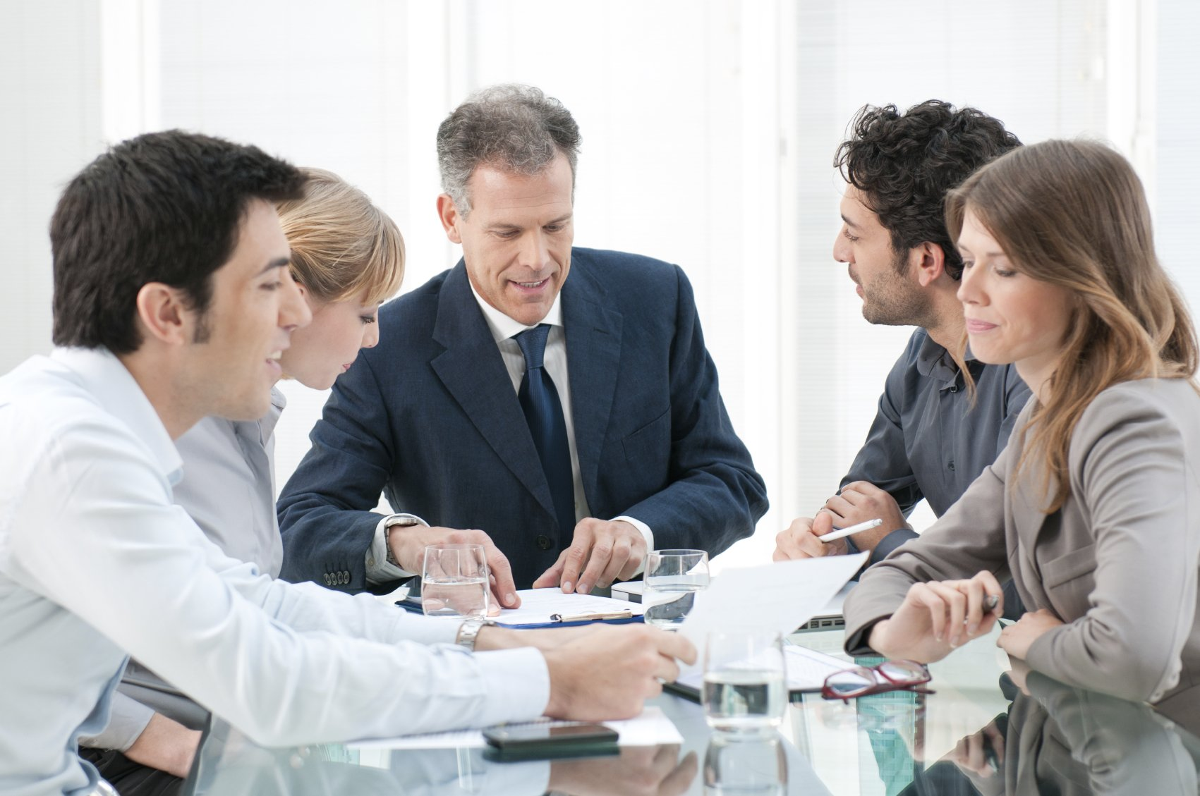 Mature businessman working and discussing with his colleagues at office